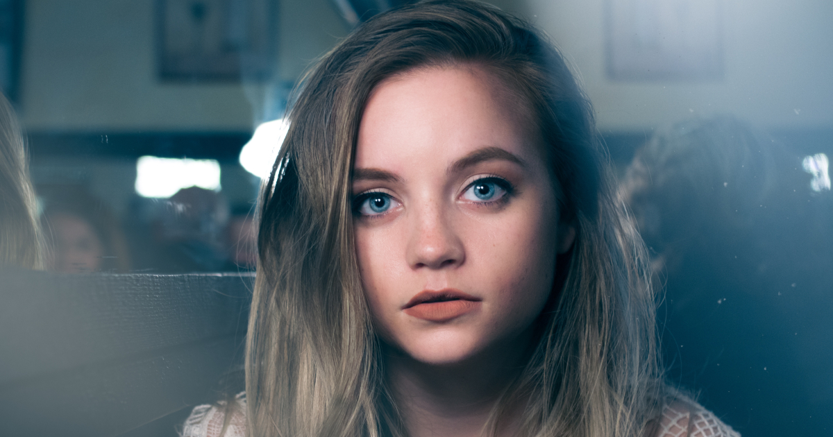 Young girl with piercing blue eyes looking directly into the camera