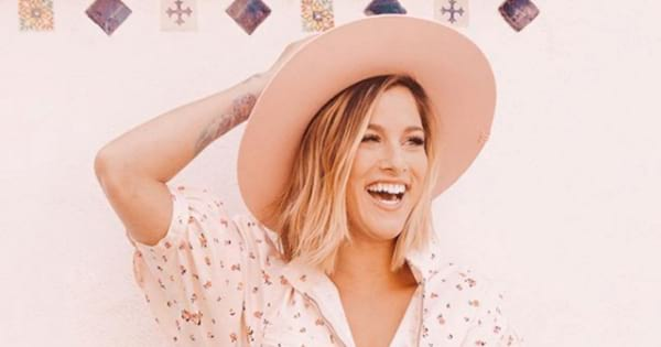 Cassadee Pope posing in front of a pink wall with a pink cowboy hat on