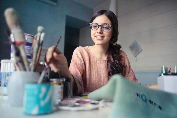 girl painting at a desk with a paintbrush in her hand