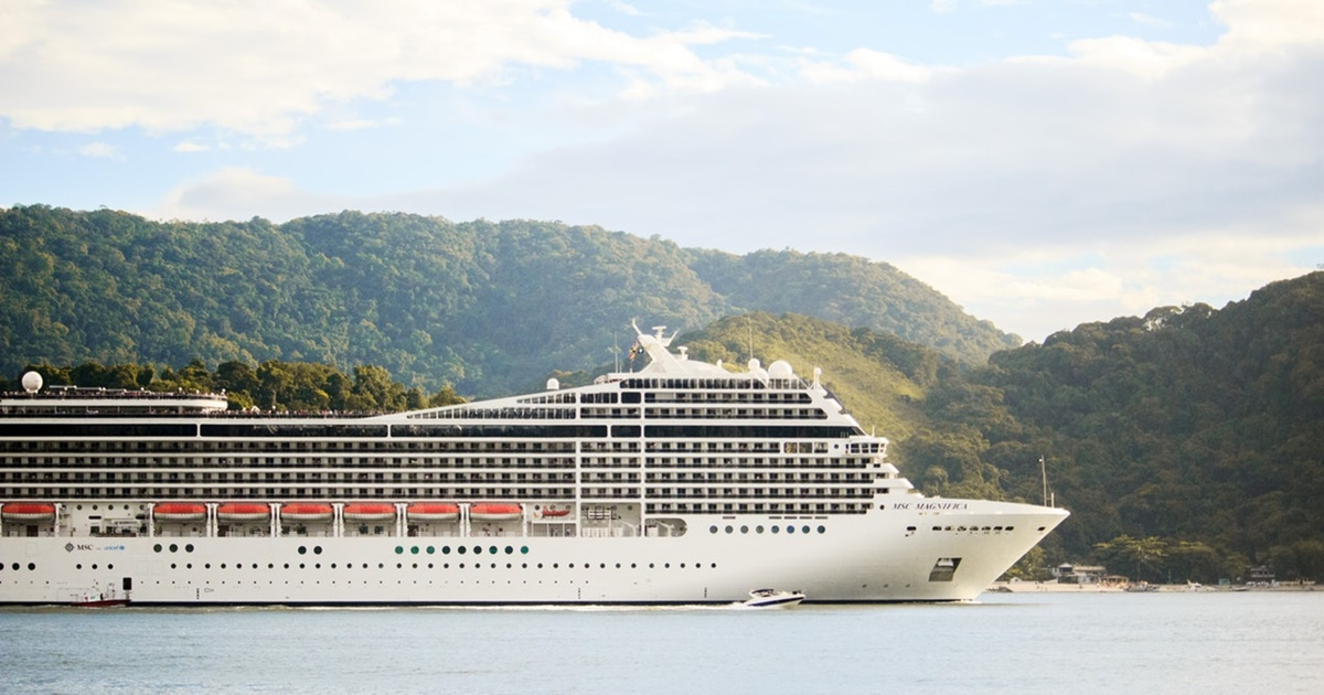 White cruise ship sailing by with tree-covered hills in the background., science & tech, travel