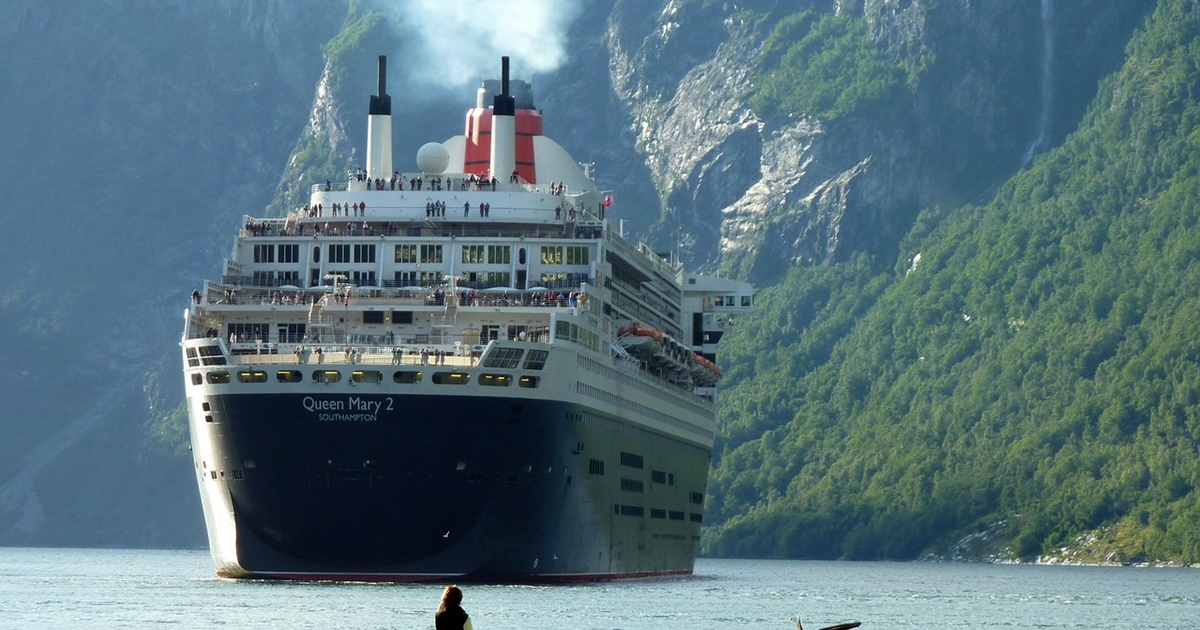 Closeup of a black cruise ship called Queen Mary 2.  Tree-covered hills are visible in the background., science & tech, travel
