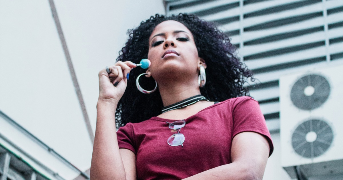 A woman looking down at the camera holds a lollipop in her hand. She has on a maroon t-shirt and large silver hoops., science & tech, food & drinks