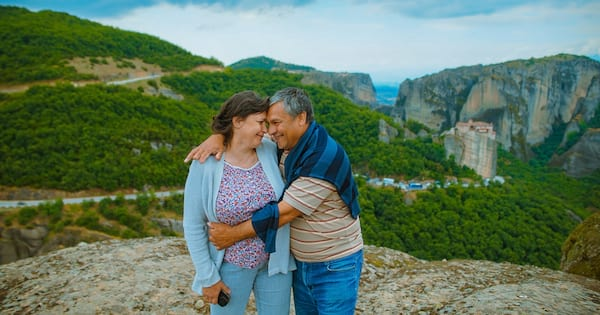 Middle aged couple embracing and standing in front of mountains., science & tech, relationships