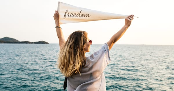 Girl standing in front of the ocean holding a white flag with the word \freedom\ written on it over her head