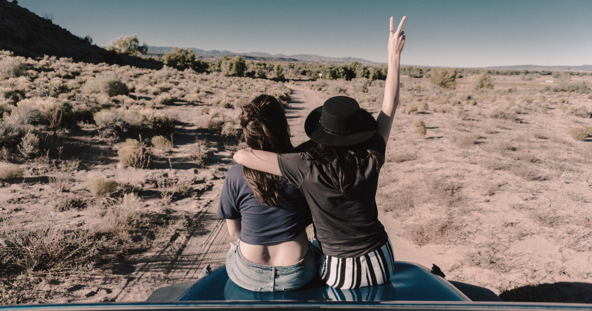 Two girls sitting on the hood of a car looking at the desert in front of them