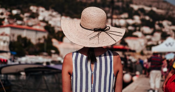 Female wearing a straw hat and striped shirt with her back to the camera
