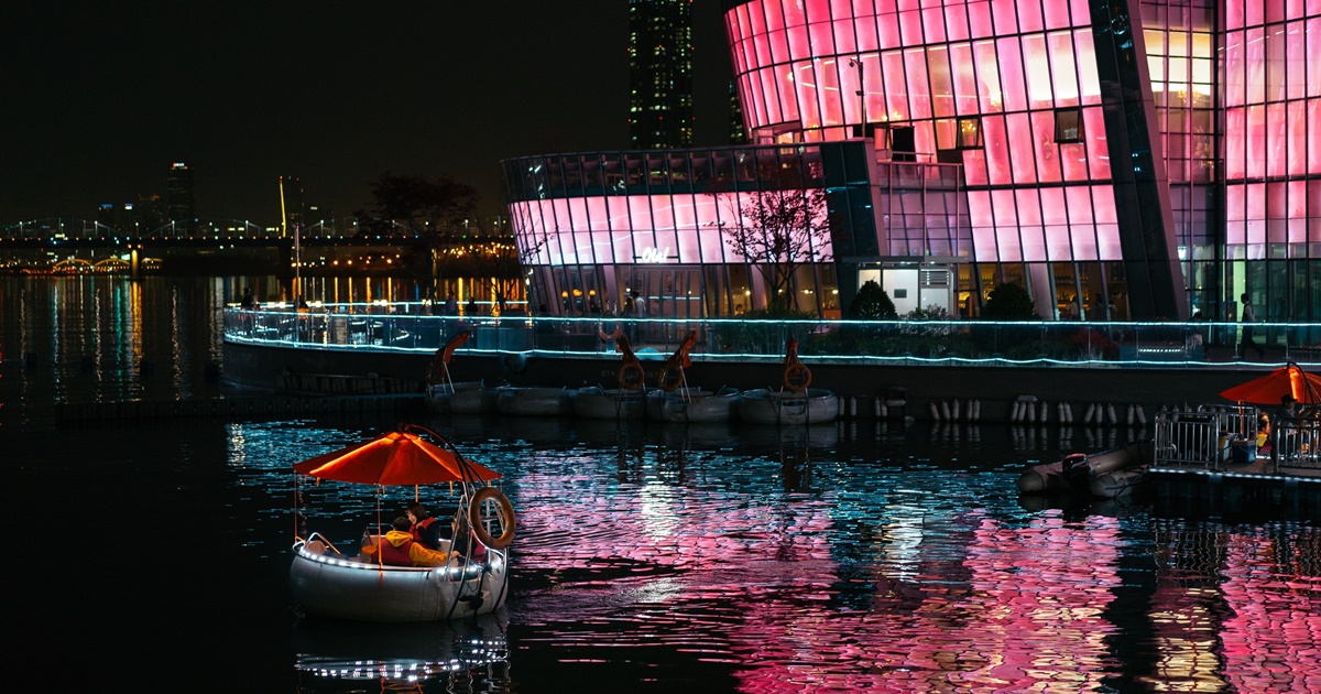 Seoul at night. A small boat on a waterway. Light from a building casts pink light on the the water., science & tech, travel