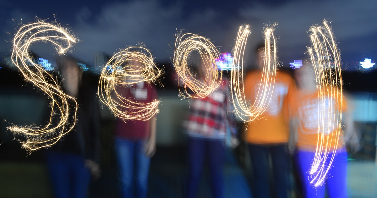 Seoul spelled out in English with sparklers. Five people are blurry but visible in the background., science & tech, travel