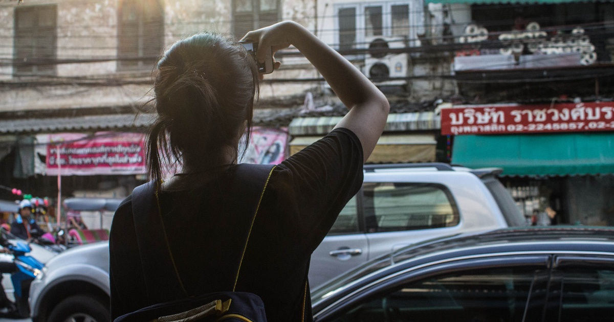 The back of a woman taking a photo in Bangkok., science & tech, travel