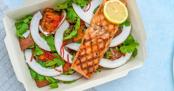 Salad in a to-go box with salmon on top of it