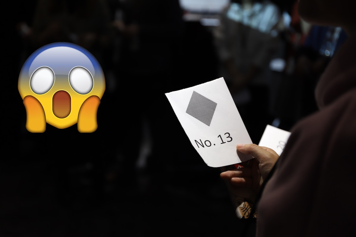 man holding a card with no. 13 on it and a screaming emoji in the left corner