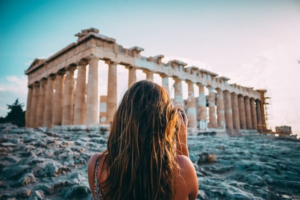 girl pointing her camera at the acropolis in Athens