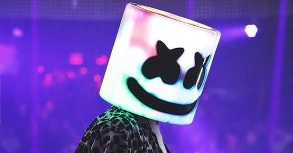 Marshmello wearing his helmet all light up while DJing