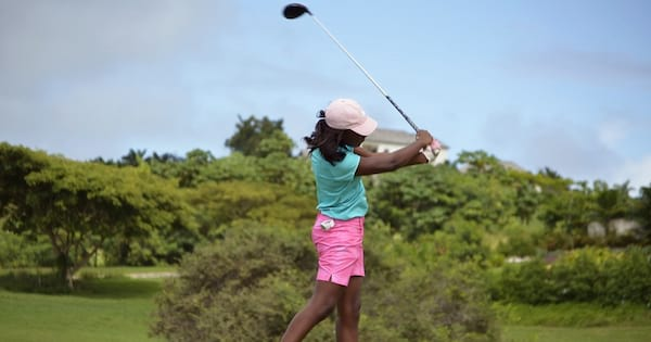 Woman swinging a golf club. She is wearing a turquoise shirt and hot pink shorts., science & tech, beauty