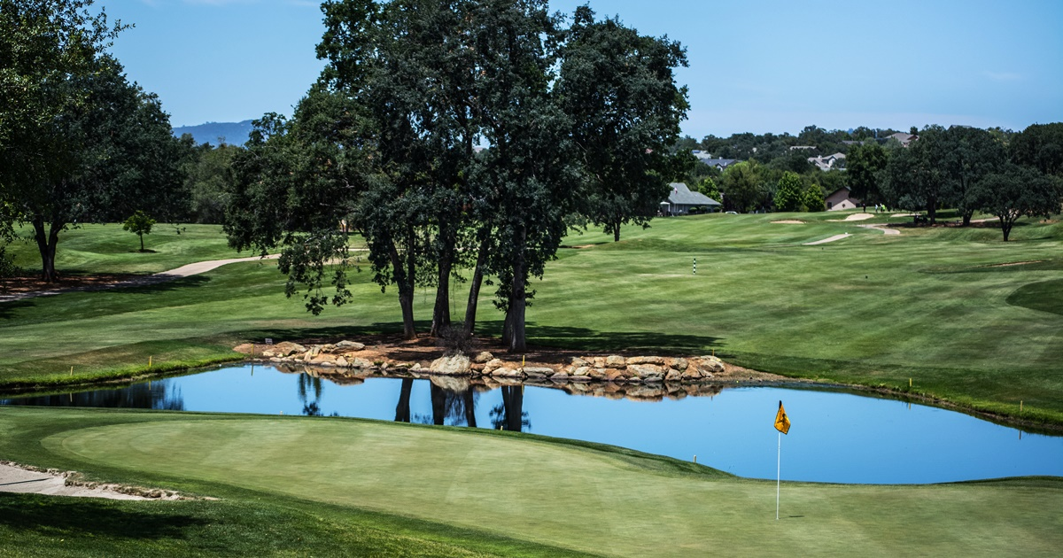 Photo of a golf course. A pond, various trees, and the sky are visible in the distance., science & tech, fitness
