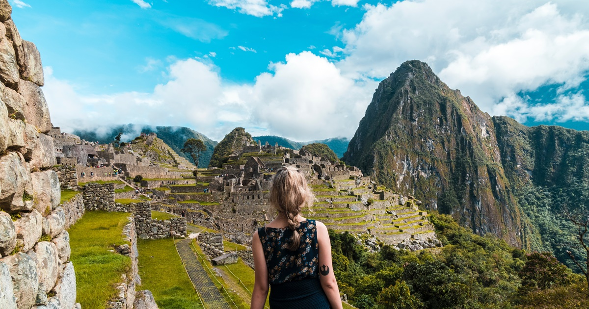 The back of a woman with the city of Machu Picchu visible in the distance., science & tech, travel