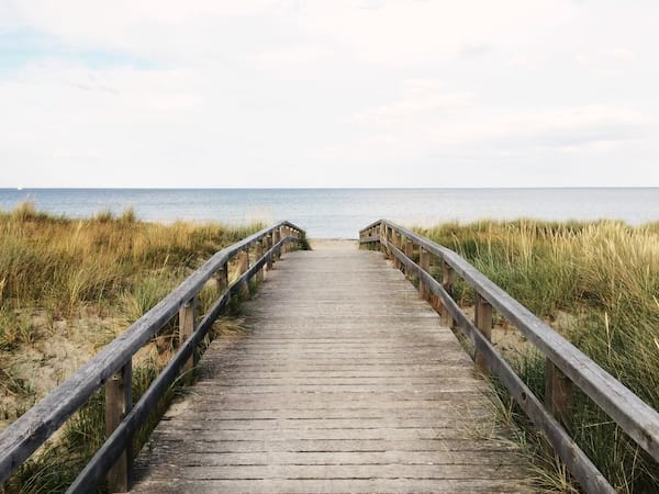 dock with beach grass surrounding it leading to the sand and ocean