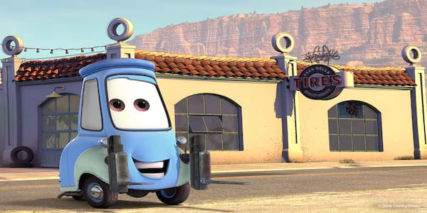 Guido from Pixar's Cars stands next to his tire shop, movies
