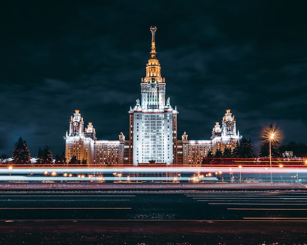 Russian building with cars zooming past at night