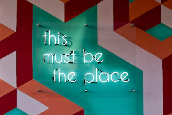 this must be the place neon sign on a colorful green, orange, and pink wall