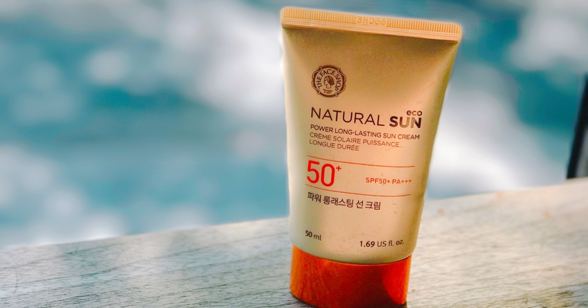 SPF 50 sunscreen sitting on a wooden ledge overlooking the ocean