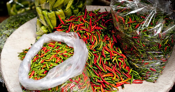 Large bags of red and green peppers on a table
