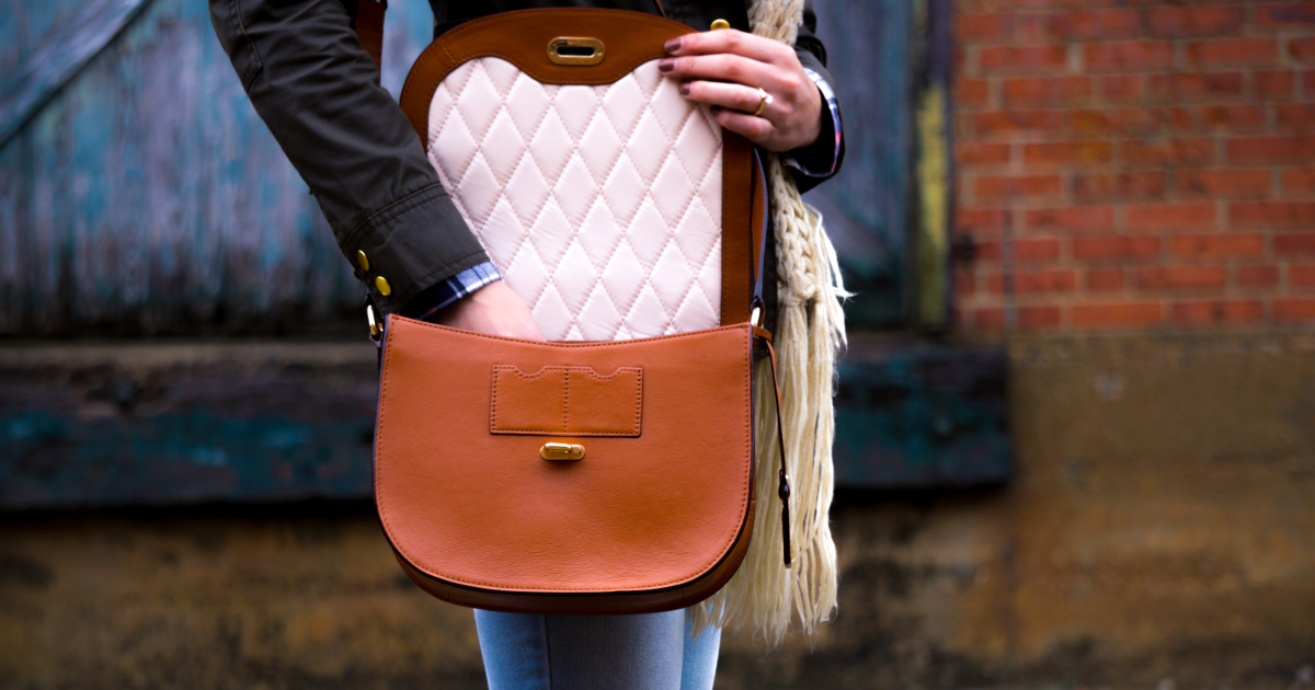 Woman taking something out of her crossbody bag