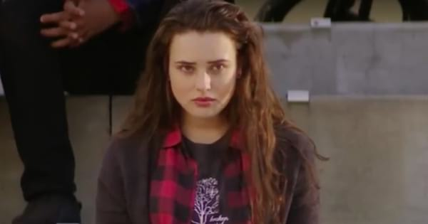 Hannah Baker sitting on the bleachers looking upset in an episode of 13 Reasons Why