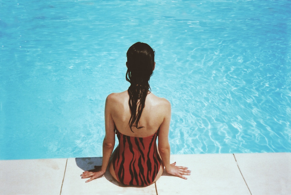 girl sitting on the edge of a swimming pull back towards camera
