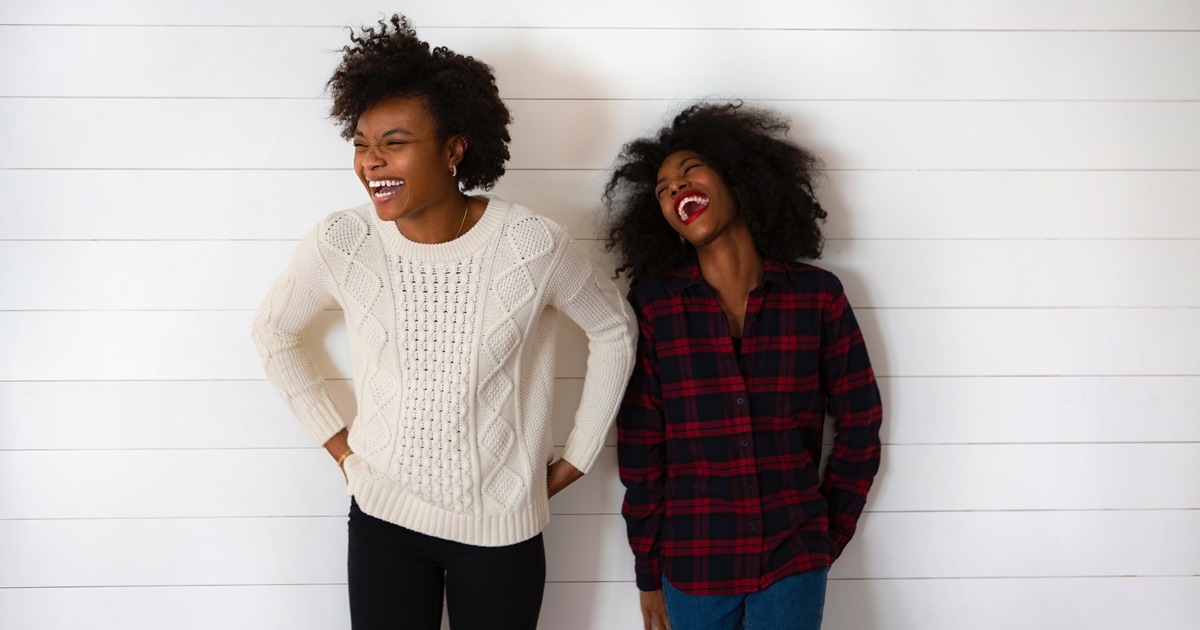 Two women smiling and leaning against a plain wall. One woman is wearing a sweater and the other is wearing a plaid shirt., science & tech, relationships