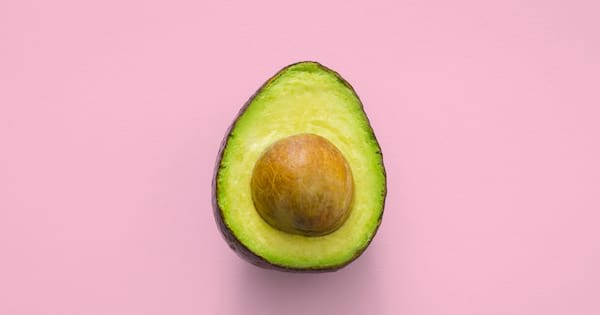 An avocado cut in half resting on a light pink background., science & tech, food & drinks