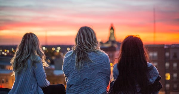 The back of three women watching the sunset., science & tech, school