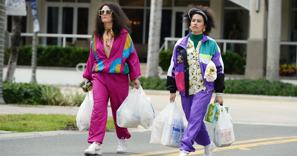 Abbi and Ilana from Broad City walk down the street carry several grocery bags. They are both wearing bright wind suits., science & tech, pop culture, tv
