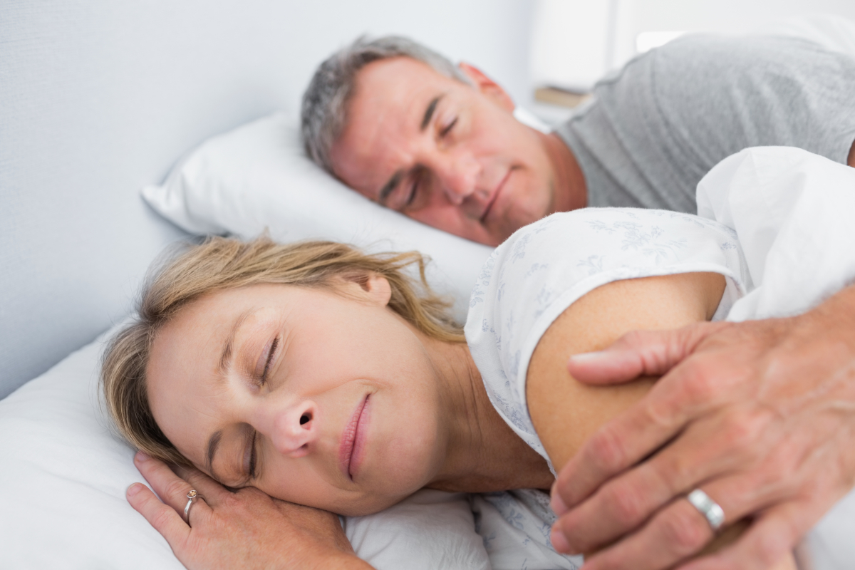 Older couple spooning in bed together