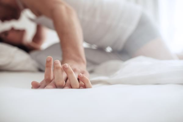Couple in bed together engaging in foreplay