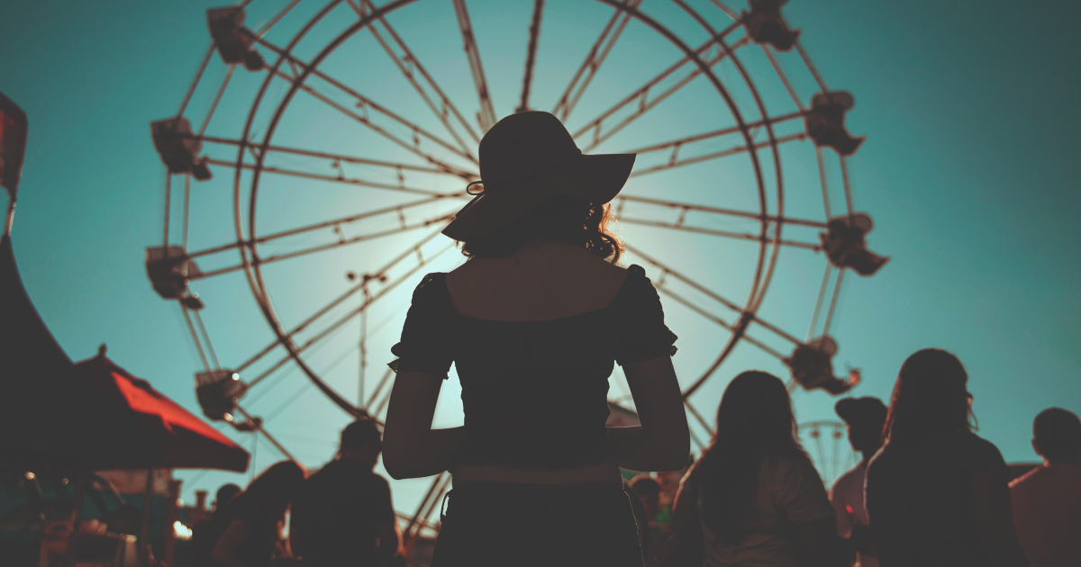 Girl standing in front of a Ferris wheel