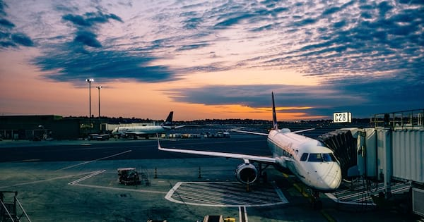 An airplane on the runway. The sun sets in the background., science & tech, travel