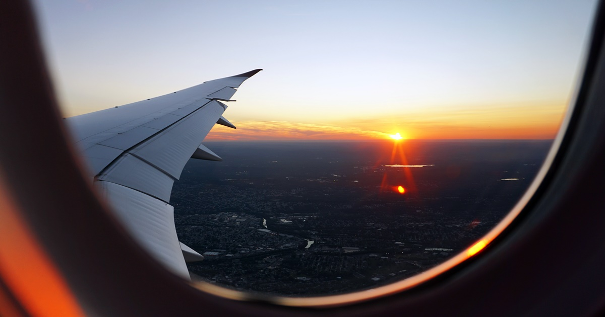 Photo taken from an airplane window. The wing and setting sun are visible., science & tech, travel