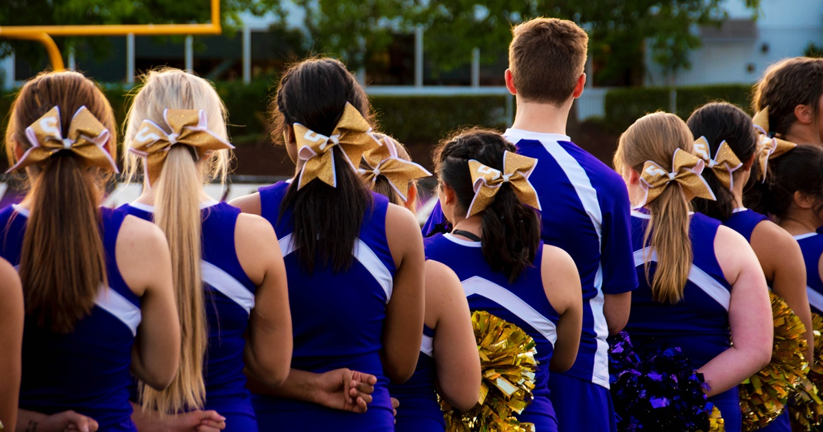 A line of cheerleaders dressed in blue and white uniforms facing away from the camera., science & tech, school