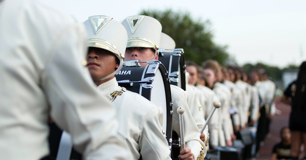 A marching band wearing white uniforms., science & tech, school