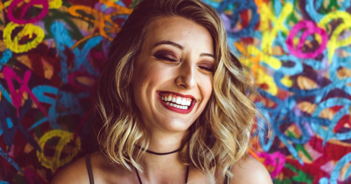 Closeup of woman laughing. She has wavy blonde hair and red lipstick on., science & tech