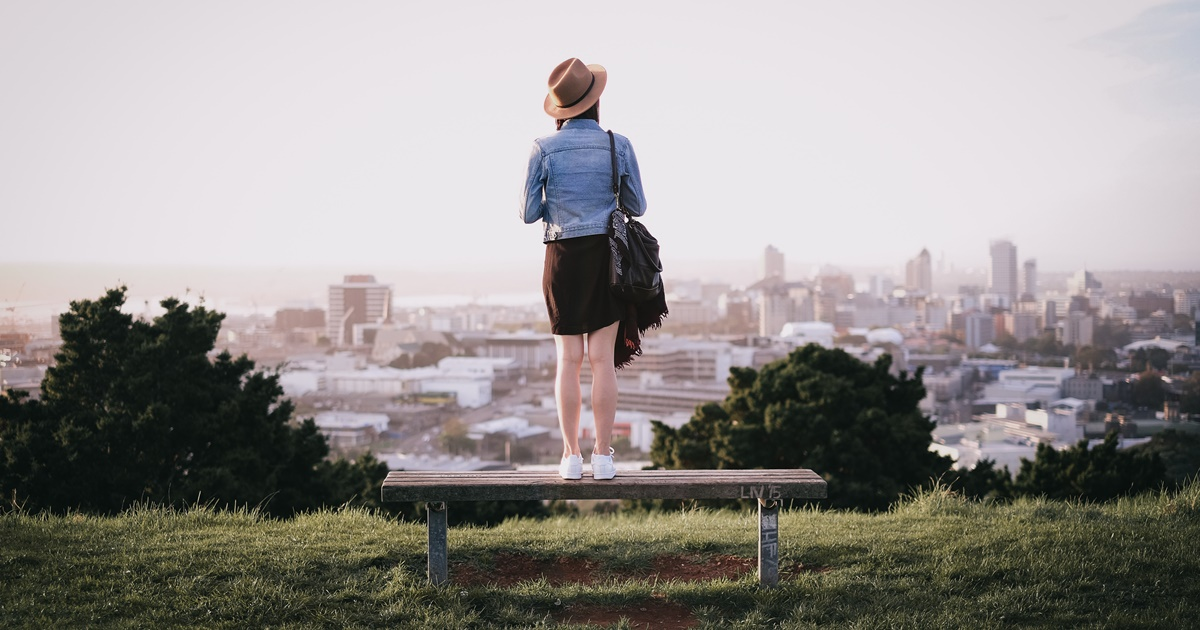 Woman standing on a bench overlooking Auckland, science & tech, travel, New Zealand, new zealand instagram captions