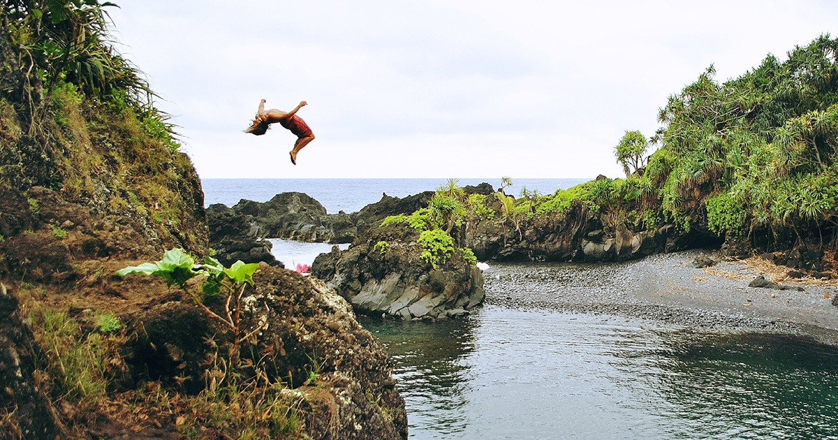 Person doing a flip off a ledge into water below in Maui, Hawaii., science & tech, travel