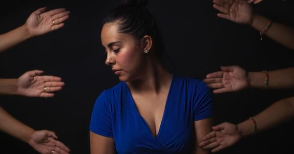 Woman wearing a blue dress looking down as arms reach out to help her