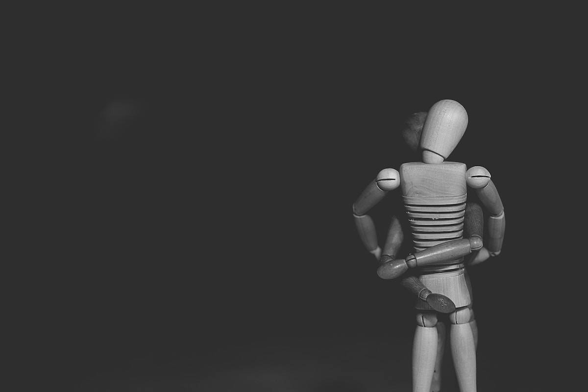 two figures holding each other in black and white