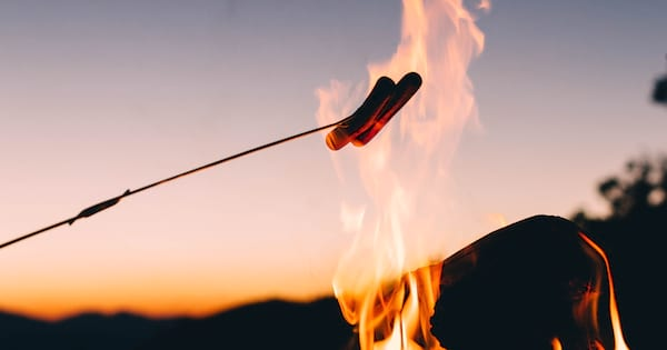 Someone roasting a hot dog over the fire., science & tech, food & drinks
