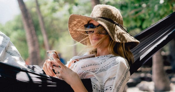 A woman smiling while lying in a hammock on Relaxation day., science & tech, health