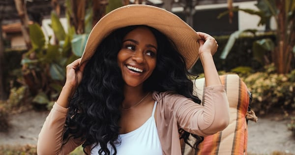 A woman smiling and holding onto her sun hat., science & tech, health