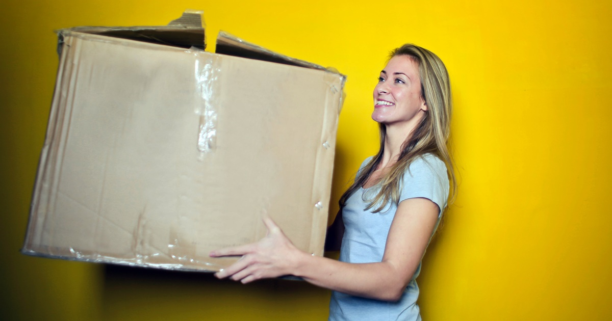 Woman carrying a large box while moving., science & tech, travel