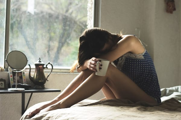 Sad girl sitting on the edge of her bed with a cup of coffee in her hand